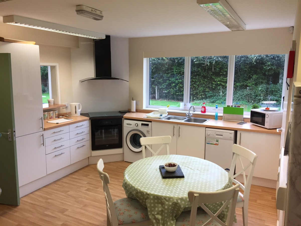 Clean, contemporary kitchen with table and green and white polkadot table cloth